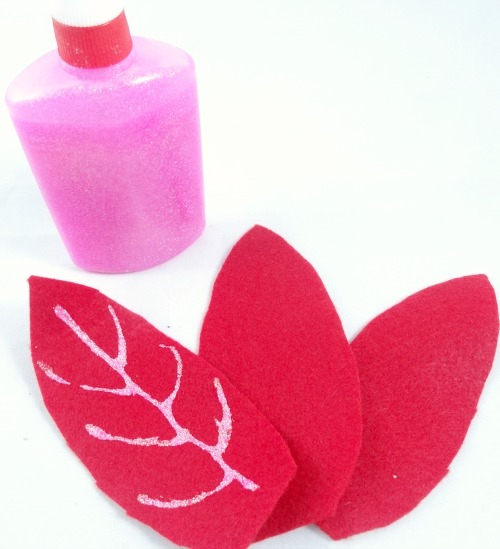 Use pink glitter glue for the veins of your poinsettia ornament
