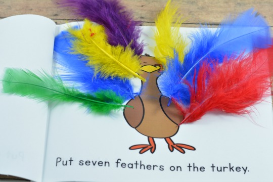 Putting feathers on the turkey in this free printable book.