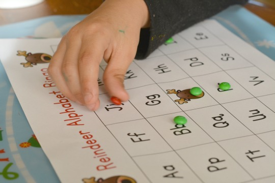 Playing Reindeer Alphabet Bingo with holiday candies. A great Christmas party activity for kids.